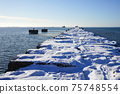 winter seascape, port entrance with snow covered concrete breakwater 75748554