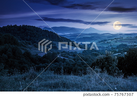 mountainous rural landscape at night. beautiful scenery with forests, hills and meadows in full moon light. ridge with high peak in the distance. village in the distant valley 75767307