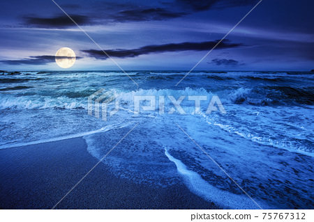sea tide on a cloudy sunrise. green waves crashing golden sandy beach in full moon light. storm weather approaching. summer holiday concept 75767312