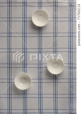White empty drinking bowls on checkered tablecloth 75768218