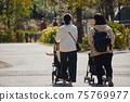 年輕的父母和孩子在嬰兒推車在春天公園散步 75769977