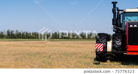 Red tractor on a field 75776323