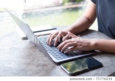 Close up female hands of a business freelance using laptop computer, searching in cafe. 75776839