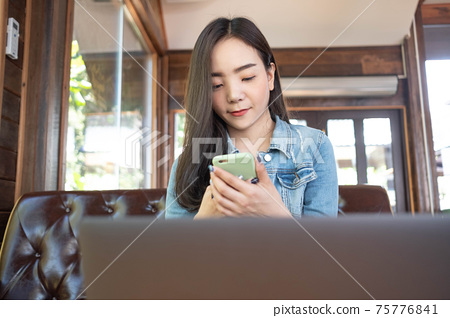 Asian female reading text message or social media on cell telephone during in modern cafe. 75776841