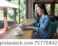 Business woman using laptop computer and drinking coffee in modern cafe. 75776842