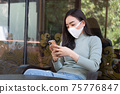 Asian female reading text message or social media on cell telephone during in modern cafe. 75776847
