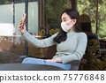 Young woman wearing medical mask making selfie or video call with smartphone at coffee shop. 75776848