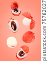 Flying fresh lychee fruits on coral colour background 75782027