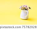 Beautiful daisy flowers in ceramic white vase on illuminating background from above 75782028