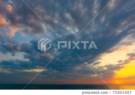dynamic cloudscape in summer at sunrise. dark clouds on the sky in yellow and pink morning light. dramatic weather condition, picturesque scenery above the sea 75801487