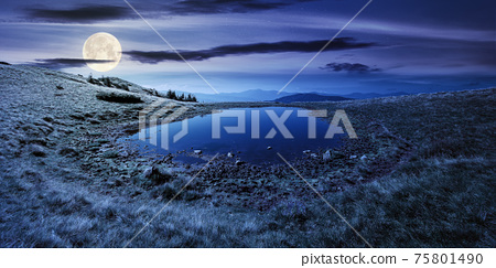 pond on the mountain meadow at night. wonderful summer landscape in full moon light. grass and trees on the hills. ridge in the distance. beautiful wide panorama 75801490