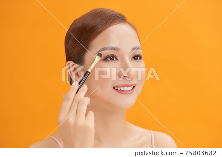 Beautiful woman using brush for eyeshadow. Photo of woman with perfect makeup on yellow background. Beauty concept 75803682