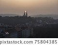 Aerial view over Prague 2 district from Nusle bridge, with typical architecture, old defense wall of Vysehrad castle and Basilica of St. Peter and Paul with orange sun between church towers in haze 75804385
