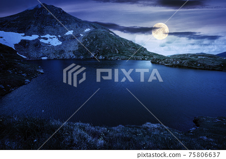summer scenery with lake on high altitude at night. beautiful landscape of fagaras mountain ridge in summer. open view in to the distant peak beneath a fluffy clouds in full moon light 75806637
