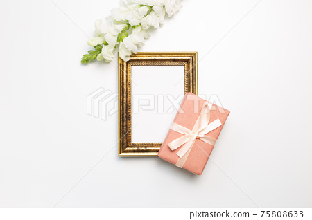 Anniversary concept. Empty photo frame with gift, snapdragon flowers on white background. flat lay, top view, copy space 75808633