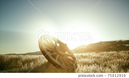 Old wooden wheel on the hill at sunset 75812910