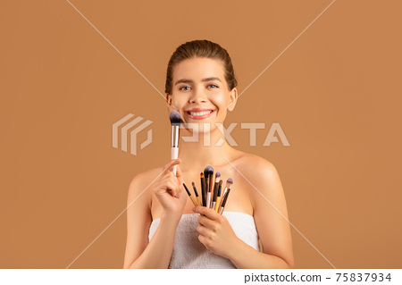 Portrait of happy young woman with smooth skin holding collection of makeup brushes over brown studio background 75837934