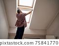 Repairman with measuring tape next to skylight window 75841770
