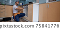 Young caucasian worker measuring drawer in kitchen furniture 75841776