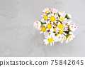 Beautiful daisy flowers in ceramic white vase on ultimate gray background from above 75842645
