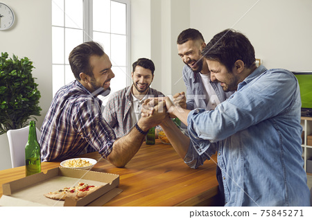 Cheerful company of male friends at home drinking beer and competing in arm wrestling. 75845271