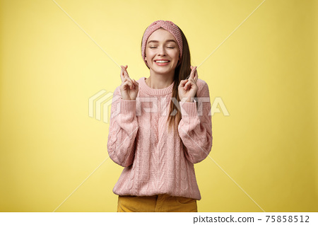 Girl wishing wellness wanting dream come true, cross fingers dreamy, close eyes waiting miracle, anticipating good news, posing excited and joyful against yellow background in knitted warm sweater 75858512