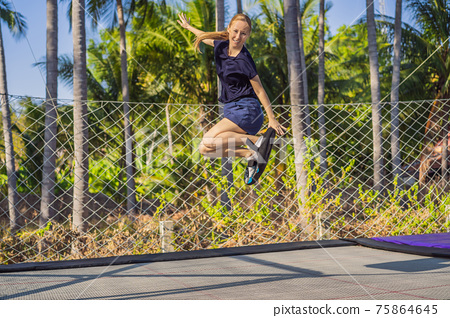 Young woman on a soft board for a trampoline jumping on an outdoor trampoline, against the backdrop of palm trees. The trampoline board is like a wakeboard, skateboard or snowboard trainer to hone 75864645