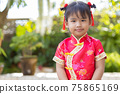 Baby girl in red Chinese outfit to celebrate Chinese new year on blurred green garden background 75865169