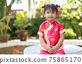 Baby girl in red Chinese outfit to celebrate Chinese new year on blurred green garden background 75865170