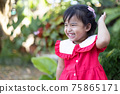 Cute asian baby girl smiling with happiness on blurred green garden background 75865171