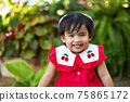 Cute asian baby girl smiling with happiness on blurred green garden background 75865172