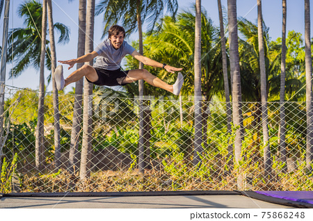 Happy man jumping on an outdoor trampoline, against the backdrop of palm trees 75868248