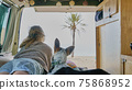 girl and her dog on a bed of a self converted camper van looking through the window living van life 75868952