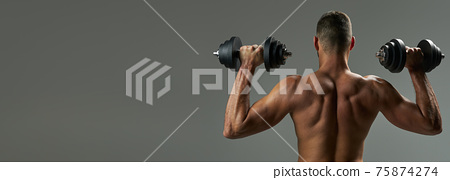 Website header of Adorable strong bodybuilder doing building up muscles with dumbbells in room indoors 75874274