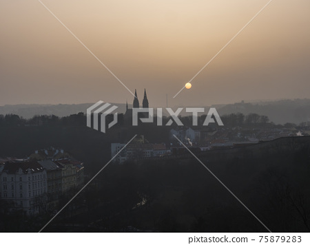 Aerial view over Prague 2 district from Nusle bridge, nuselsky most with typical architecture, old defense wall of Vysehrad castle and Basilica of St. Peter and Paul towers with orange sun in haze 75879283