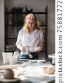 A young european beautiful female potter in a creative process of making ceramics at table in workshop. Hair fluttering in the wind at sunny day at pottery studio. 75881772