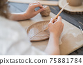 Close up of female potter holding stick and making ornament on earthenware. Clay master moulding clay product. Concept of ceramic art and hobby. 75881784