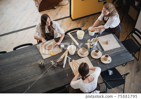 Beautiful young female artist girls creating handmade pottery in modern art studio. Education kids and parents. 75881795