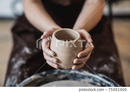 Hands of a potter, creating an earthen jar on the circle 75881800