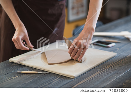 Close up of skilled craftswoman removing part of clay while making ceramic product in pottery workshop 75881809