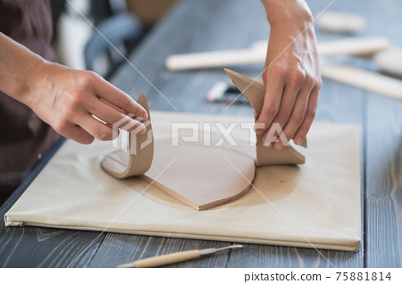 Close up of skilled craftswoman removing part of clay while making ceramic product in pottery workshop 75881814