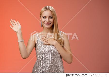 Happy blond girl say hi introduce herself boyfriend friends raise hand waving hello hi gesture press palm chest sincere smiling broadly tell truth swearing, promise keep secret friendly gaze camera 75885920