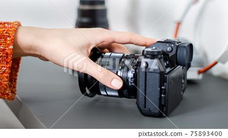 Female hand taking a camera 75893400