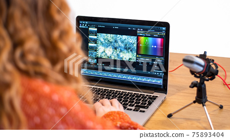 Young content creator girl editing video on her laptop 75893404
