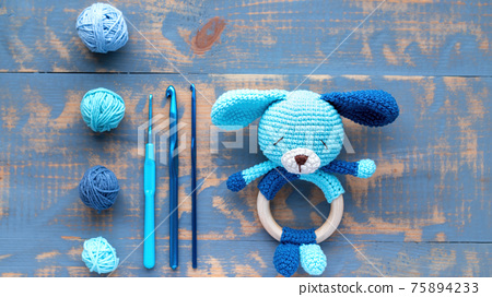 Knitted blue toy for kids on the table 75894233