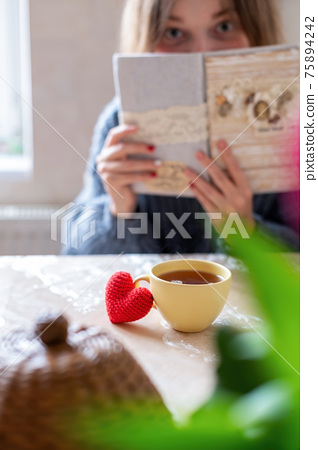 Knitted red heart and a cup of tea 75894242