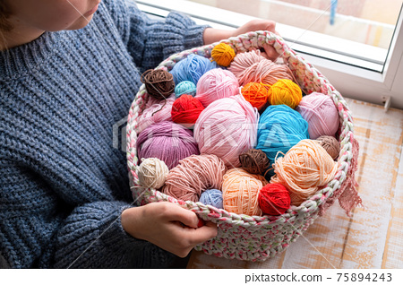 Woman holding knitted couch with yarn balls 75894243