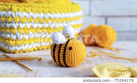 Knitted yellow bee toy on the table 75894279