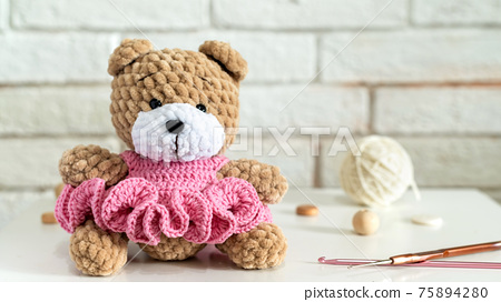 Knitted teddy bear on the table 75894280