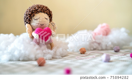 Cute knitted plush toy on the sofa 75894282